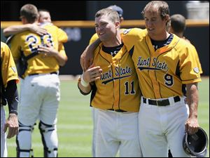 Kent State's Joe Koch (11), assistant coach Doug Sanders (9) and others react after losing 4-1 to South Carolina in an NCAA College World Series elimination baseball game in Omaha, Neb., Thursday.