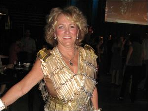 Cindy Folger models a golden glass covered gown.