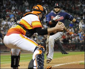 Houston Astros catcher Chris Snyder, left, waits with the ball to keep Cleveland Indians' Carlos Santana from scoring in the seventh inning of a baseball game Friday, in Houston. The Indians won 2-0.