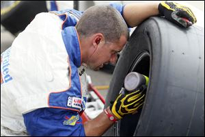 A crew member for the Federated Auto Parts team works on a tire during the Sprint Cup Series Quicken Loans 400 race at the Michigan International Speedway on June 18.