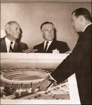 "Detroit Mayor Jerome Cavanagh, right, shows a drawing of the proposed Olympic Stadium in 1963 to George Romney, center, governor of Michigan, and Kenneth L. ""Tug"" Wilson, president of the Olympic committee."