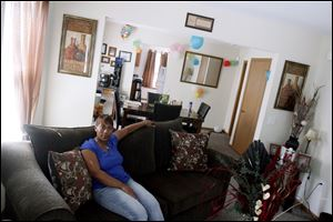 Stacy Madden, 35, poses in the living room of her 2-year-old home which was developed by the United North Community Development Corp.