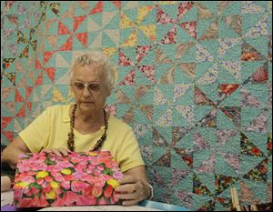 "Juanita Emerson, of Perrysburg, creating a ""gracious gift box"" in front of a quilt she donated to the shop."