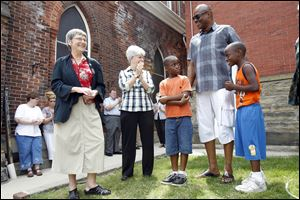 Sisters Simone Campbell, left, and Reg McKillip talk with Terry Crosby, educatio