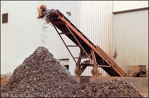 Scrap steel coming off conveyor shredded as finished product at OmniSource Corporation.