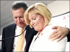 Kasich, left, pust his arm around Rep. Teresa Fedor as she speaks to supporters.