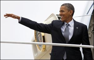 President Barack Obama waves as boards Air Force One
