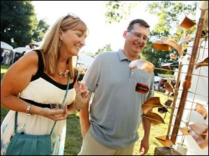 Brent and Michele Rice of Lambertville, Ohio, admire the sculptures in the Classic Copper booth.