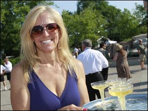 Julie Cousino passes out champagne at ZOOtoDO.