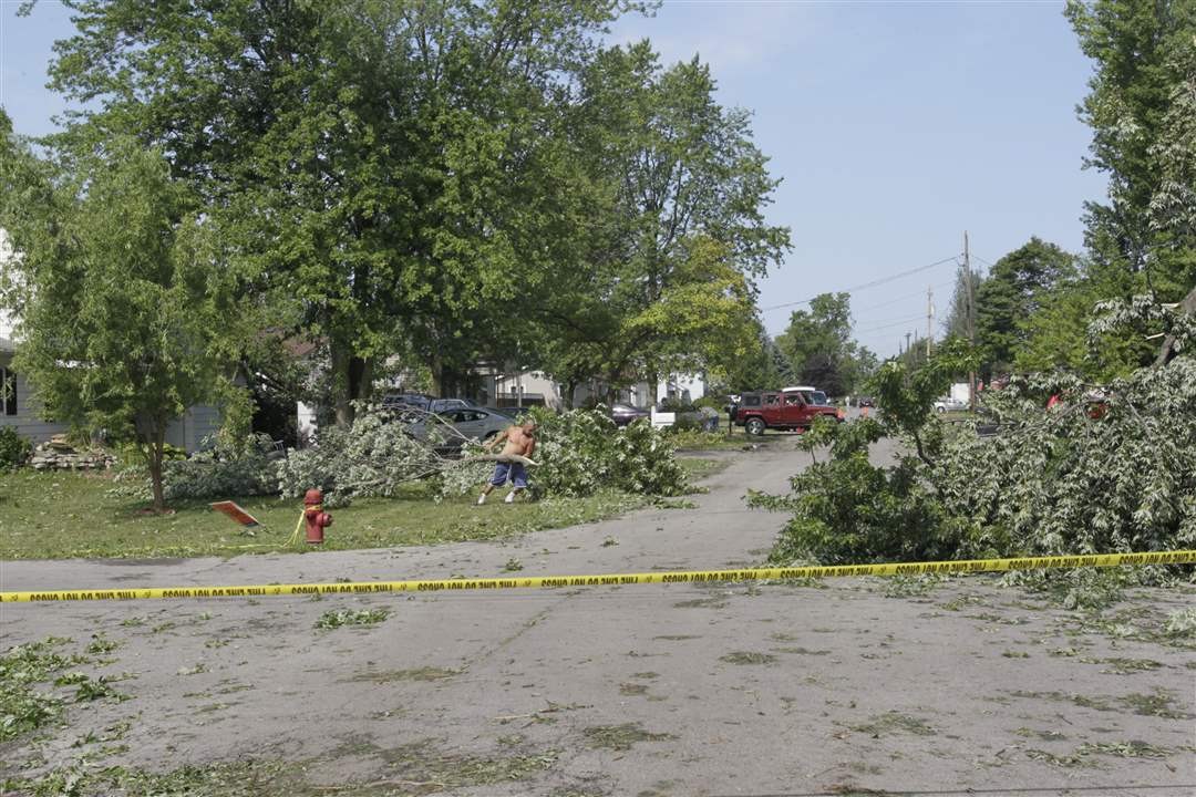 Rudy-Ochoa-of-Findlay-clearing-a-branch-that-fell-in-the-yard