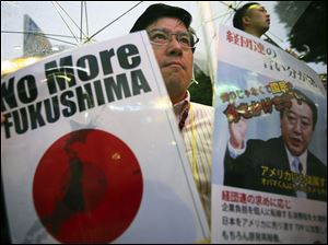 A participant holds a slogan and a photo of Japanese Prime Minister Yoshihiko Noda during a rally protesting the restart of Ohi nuclear power plant, in Tokyo, Sunday.