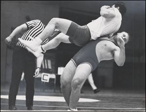 Greg Wojciechowski hoists Rogers High School's Byron Rhodes as referee Harvey Bowles officiates at the University of Toledo during Olympic trials qualifying rounds in 1968. Wojciechowski finished as runner-up for the Olympic team in 1968, 1972, and 1976. He finally made the team in 1980.