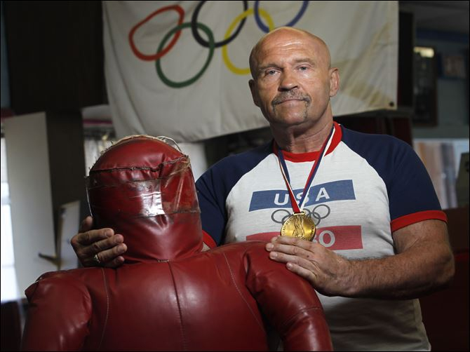 No go for Wojo Greg Wojciechowski, during a trip to the Dick Torio Health Club, wears the medal awarded to 1980 Olympians by President Jimmy Carter.