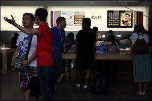 Visitors look at computer products near advertisement for Apple's iPad tablet computer at an Apple store in Beijing, China.