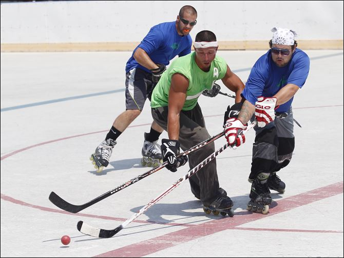 Nate Ackerman of the Golddiggers, center, and Shane O'Brien, right, of Mick Electric battle for the ball as Mr. O'Brien's teammate, Danny Kroggel, trails them during a Toledo Street Hockey League game Sunday at the Ottawa Park ice rink in Toledo. The league, which was formed in 2008, consists of 28 teams with about 300 players and has been using the rink for its games for the last three years.