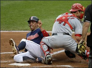 Cleveland Indians' Michael Brantley slides past Los Angeles Angels catcher John Hester to score on a sacrifice fly by