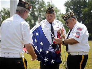 John Hall, left, Dana Swyer, center, and Juan Cantu, right, with the Northwood VFW Post 2984, raise a new flag at the Luther Ridge Senior Apartments.