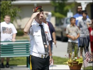John Hall, with the Northwood VFW Post 2984, salutes the flag after its raising while residents and friends of Lutheran Homes Society's Luther Ridge Senior Apartments stand behind him.