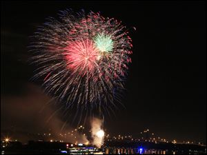 Frequent bursts of color light up the night sky for Toledoans watching the show along the river.