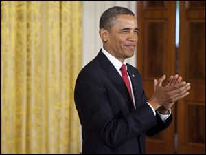 President Barack Obama applauds in the East Room of the White House for a group of U.S. service members during a naturalization ceremony.