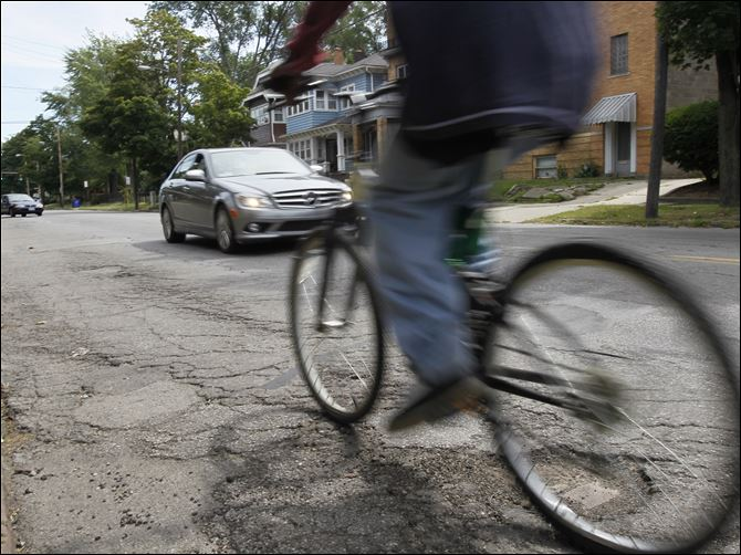 City gets $6.5M state award A bicyclist and motorists navigate over cracks and potholes on Bancroft Street near Scottwood Avenue in the Old West End.