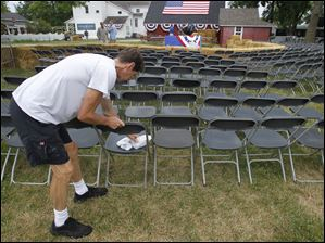 Stage hand Mike Pelechaty, of Toledo, wipes rain off seats.