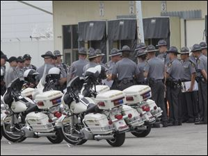 Ohio Highway Patrol troopers gather before the president's plane arrives at the airport.