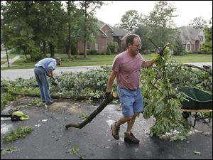 Chad Nofzinger, left, and Charles Ide, right, use chainsaws to remove downed trees from their lawn and driveway.