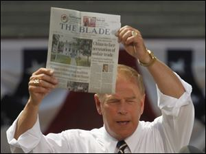 Former Ohio governor Ted Strickland holds up a Toledo Blade newspaper.