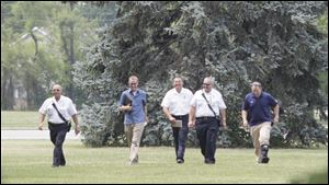 Law enforcement officers and firefighter personnel  go over the grounds in preparation for the President's visit.