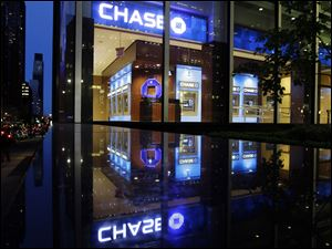 Automobiles pass JPMorgan Chase in New York City. The FDIC says fewer U.S. banks are at risk nationwide of failure for a variety of reasons: an improved economy, healthier loan portfolios, low interest rates, higher bank account fees, and a wave of mergers.