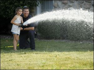 Perrysburg Firefighter Mike Hickerson assists Cadence Cosgove, 7, as she sprays a fire hose during the annual First Fridays series.