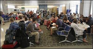Dozens of travelers wait to board at Akron-Canton Airport in late June.