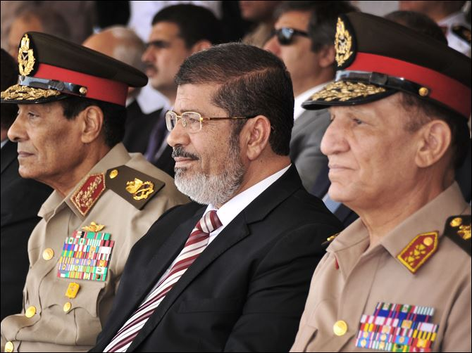 APTOPIX Mideast Egypt Egyptian President Mohammed Morsi, center, and Field Marshal Gen. Hussein Tantawi, left, attend a medal ceremony recently in Cairo. Morsi challenged the nation's military leaders Sunday by calling for Parliament to reconvene, weeks after a high court ordered the legislature to dissolve because of fears that Islamists would dominate the government.