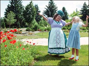 Margaret Pellegrini, one of the original munchkins, dances with Dani Hopper, 6, of Russell, Iowa, during the 1999 Judy Garland Festival in Grand Rapids, Minn. Ms. Pellegrini, who has written an unpublished memoir, above left, was 15 when she worked in 'The Wizard of Oz.'
