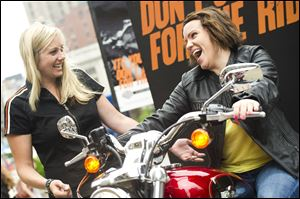 Harley-Davidson representative Dana Wilke, left, assists Lizzy Dabczynsky, 22, of Salt Lake City, Utah, in test riding a motorcycle in New York.