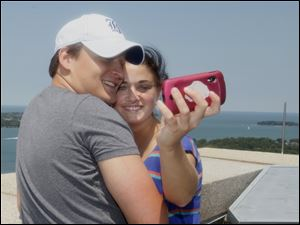 Joe Bodenbender of Put-In-Bay and his girlfriend Victoria Zakharova take a picture on top of Perry's Victory and International Peace Memorial on South Bass Island.