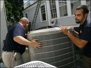 Contractors install an air conditioner in Maryland. The recent heat wave meant more air conditioning and electricity use. But long-term factors are behind a national increase in electricity prices.