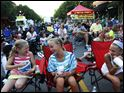 Rae Glover, 10, left, Abby Monegan, 10, center, and Kaeli Koop, 11, right, joke before the start of Thursday evening's Taking it to the Streets Movie Night in downtown Sylvania. The girls had set up camp directly in front of the projection screen several hours before the start of the movie.