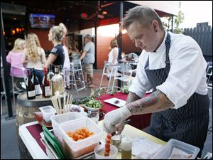 Robby Lucas, Bar 145's executive chef, prepares food on the patio Tuesday, which is a highlight of Tuesday nights. The menu items are prepared at the time of ordering; nothing is made in advance.