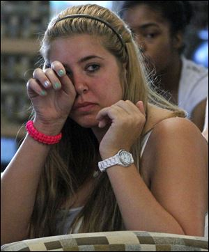 Penn State freshman Jessica Knoll of Lebanon, Pa., wipes a tear in the student HUB on the university's main campus in State College, Pa., as she listens to the televised news conference held by former FBI Director Louis Freeh. The news conference was held after the release of his group's report on the Jerry Sandusky child sex abuse scandal.