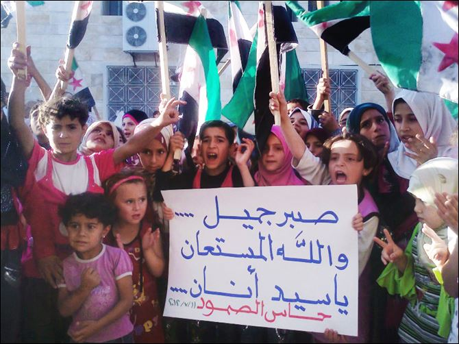 Over 200 killed in Syria as rebel area is targeted Syrian children chant slogans and hold an Arabic poster reading