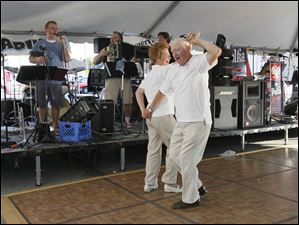 Carol Zomkowski, left, and Daniel Wozniak, both from Toledo, good friends who dance together every week. dancing to the music of Badinov under the tent just south of Czelusta Park on Lagrange. The Lagrange Street Polish Fest. The festival continues through Sunday.