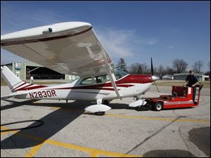A Cessna 182 is pulled out of the hangar for a flight lesson.