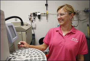 Lori Drown, a lab technician at Plastic Technologies Inc., analyzes a plastic sample on a gas chromatograph. Her employer said she and other workers most likely won't be affected by the Affordable Care Act because the firm offers a premium health plan to workers.