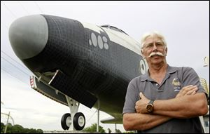 Former space shuttle worker Terry White poses in front of a mock space shuttle at the Astronaut Hall of Fame in Titusville, Fla. White was a project manager who worked 33 years for the shuttle program until he was laid off after Atlantis landed last July 21.