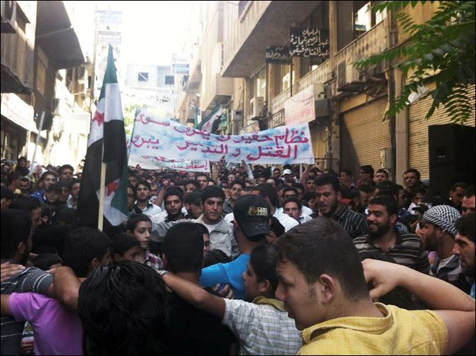 "Syrians chant during a demonstration in Damascus in this picture taken by an anonymous photographer. A partial translation of Arabic on the banner is ""a horrible regime, killing and destruction."""