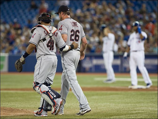 Cleveland Indians pitcher Derek Lowe, right, talks with catcher Carlos Santana during third inning Sunday in Toronto. The Indians lost 3-0 to the Blue Jays.