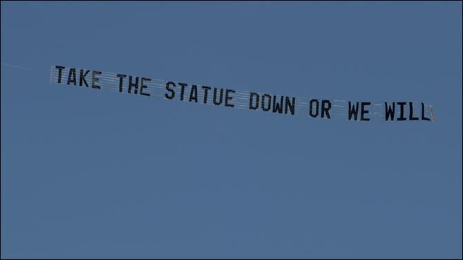 Penn State Abuse A plane flying over the Penn State University campus in State College, Pa., pulls a banner reading 'Take the statue down or we will'. The towing company is from Wood County, Ohio.