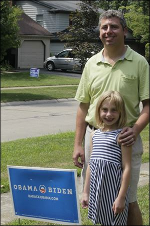 Daniel Greenberg pauses with his daughter Nina, 7, at the sign that a Sylvania zoning official ordered him to remove. Mr. Greenberg has filed a lawsuit in federal court in Toledo saying the ordinance violates his First Amendment free speech rights. The sign is to remain until a hearing Monday.